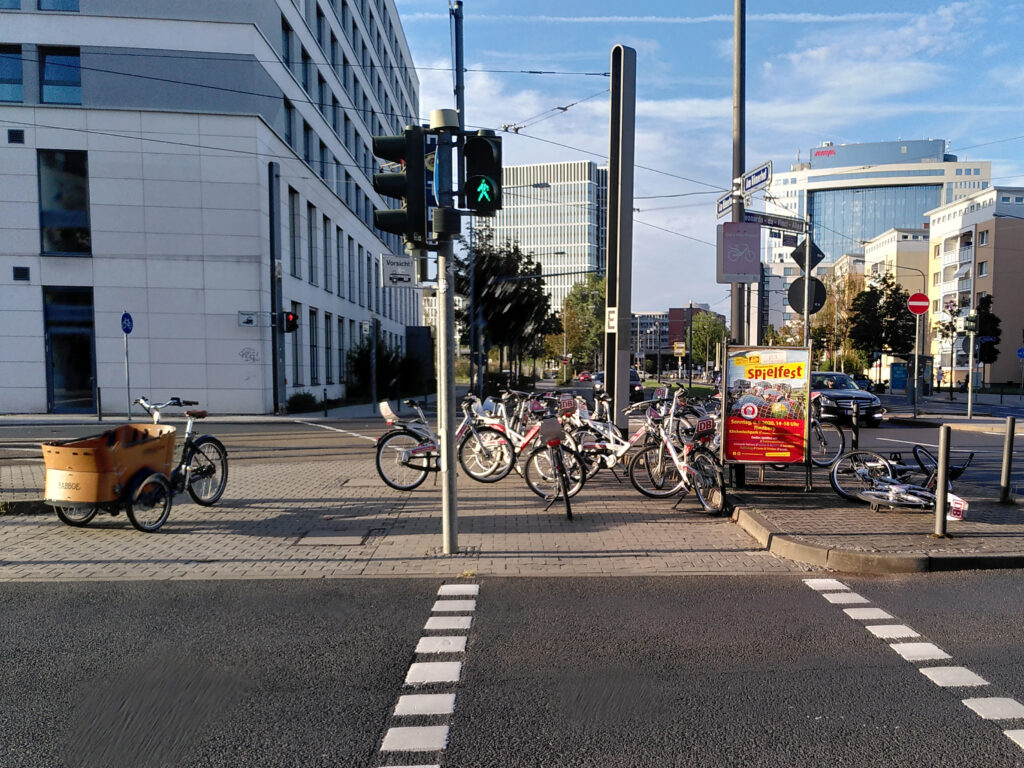 Many bicycles parked on a traffic island
