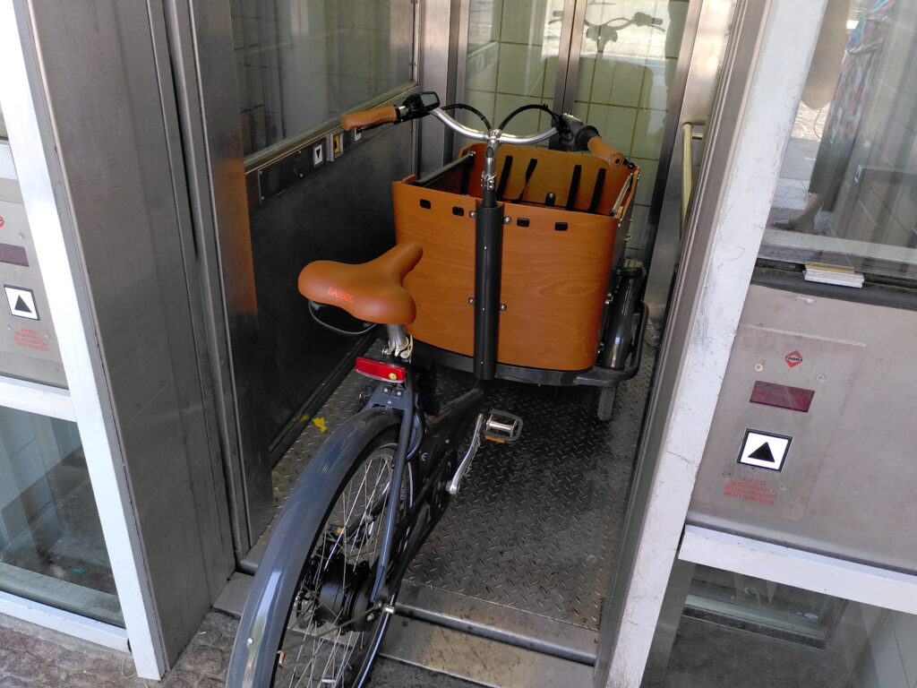 The trike in a lift, with its back wheel sticking well out of door