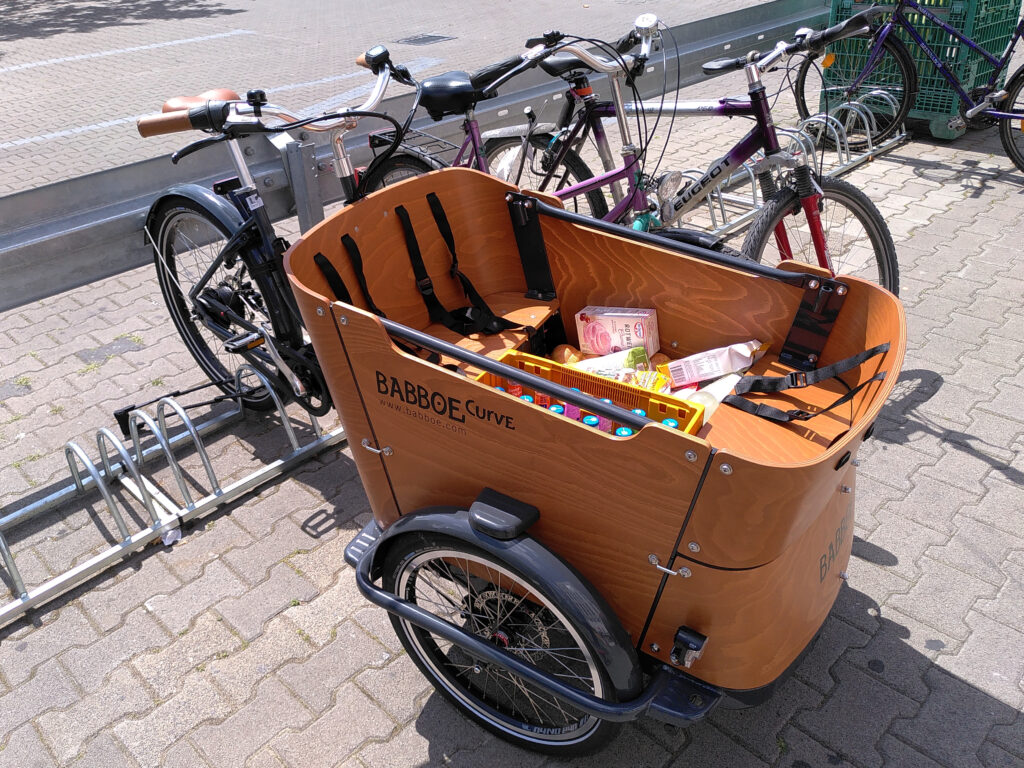 Trike with box filled with shopping, parked in a bike rack